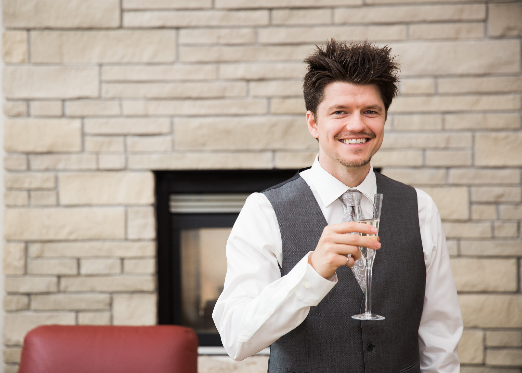groom drinking champagne on wedding day in front of fireplace