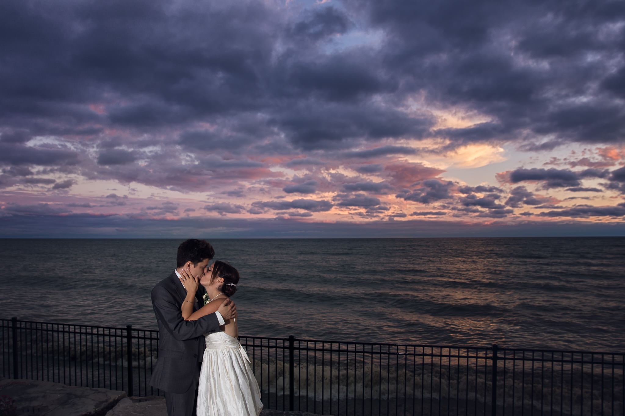 newlywed couple kissing with beautiful sunset sky by lake ontario