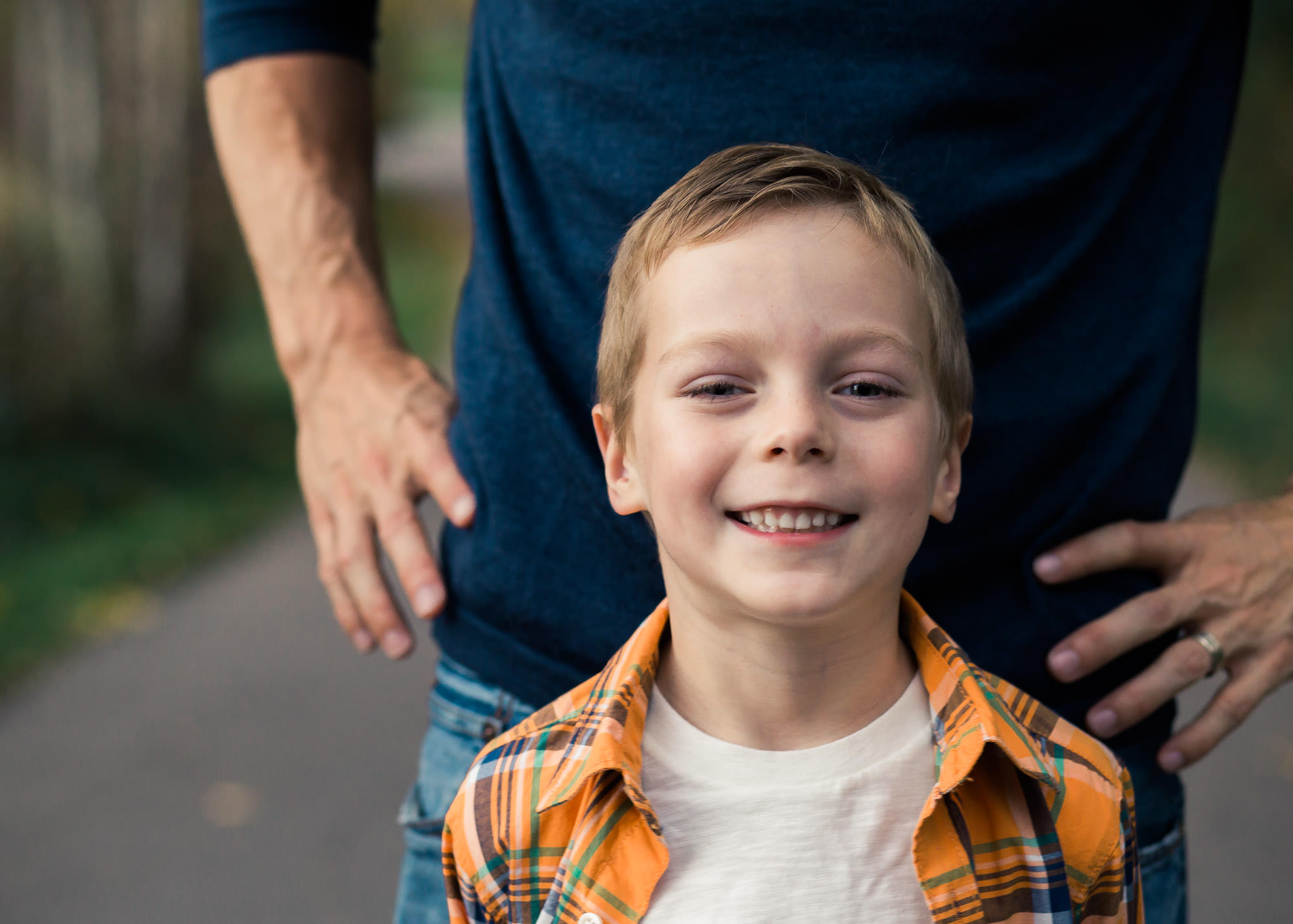 boy standing in front of father, family photo session