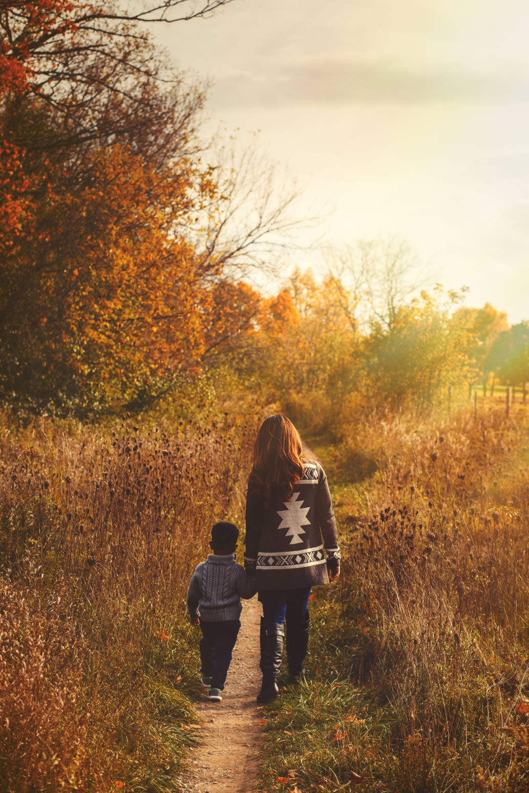 mother and son walking together holding hands in field