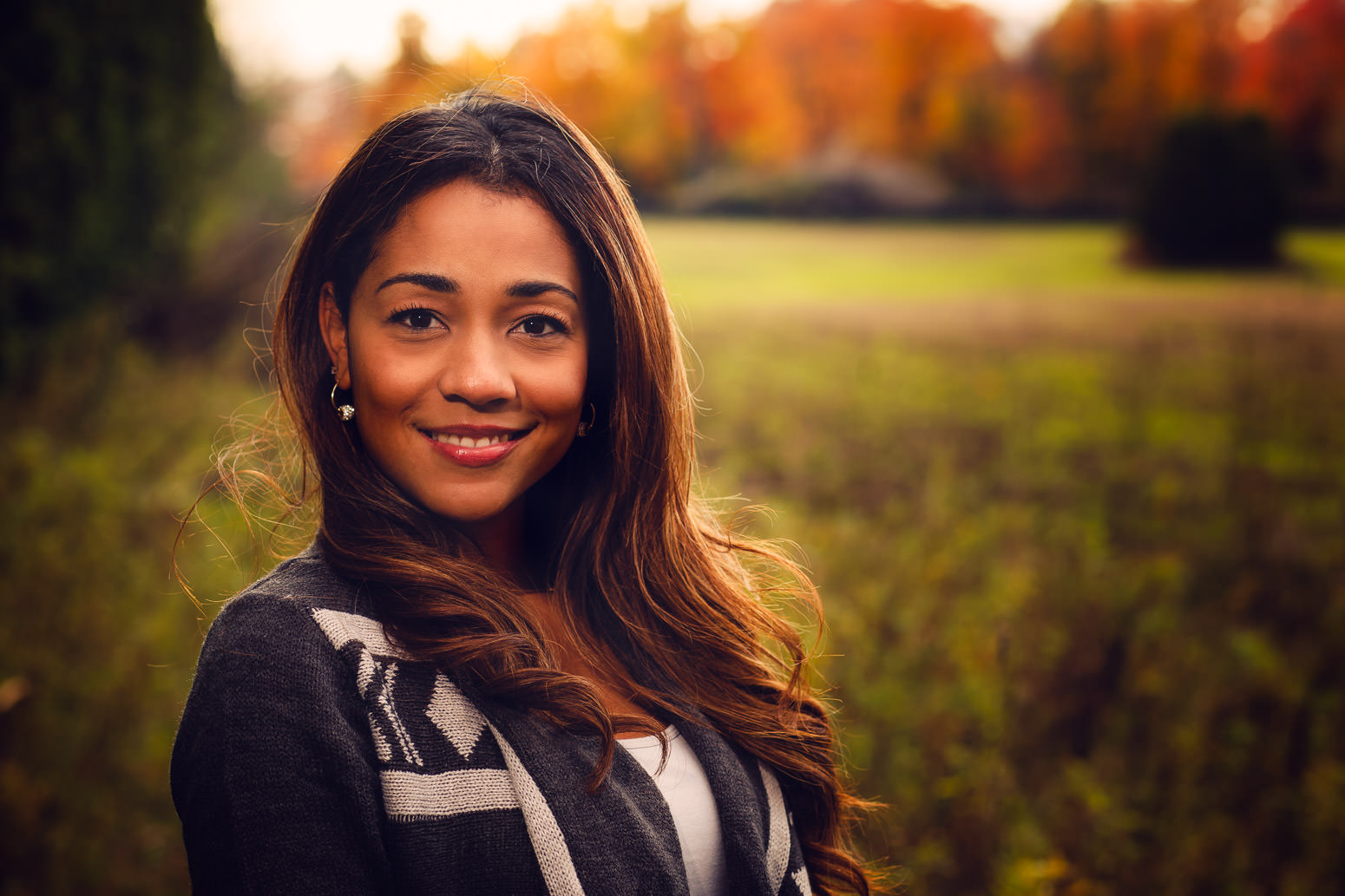 beautiful woman posed in front of field in Whitby with fall colours behind