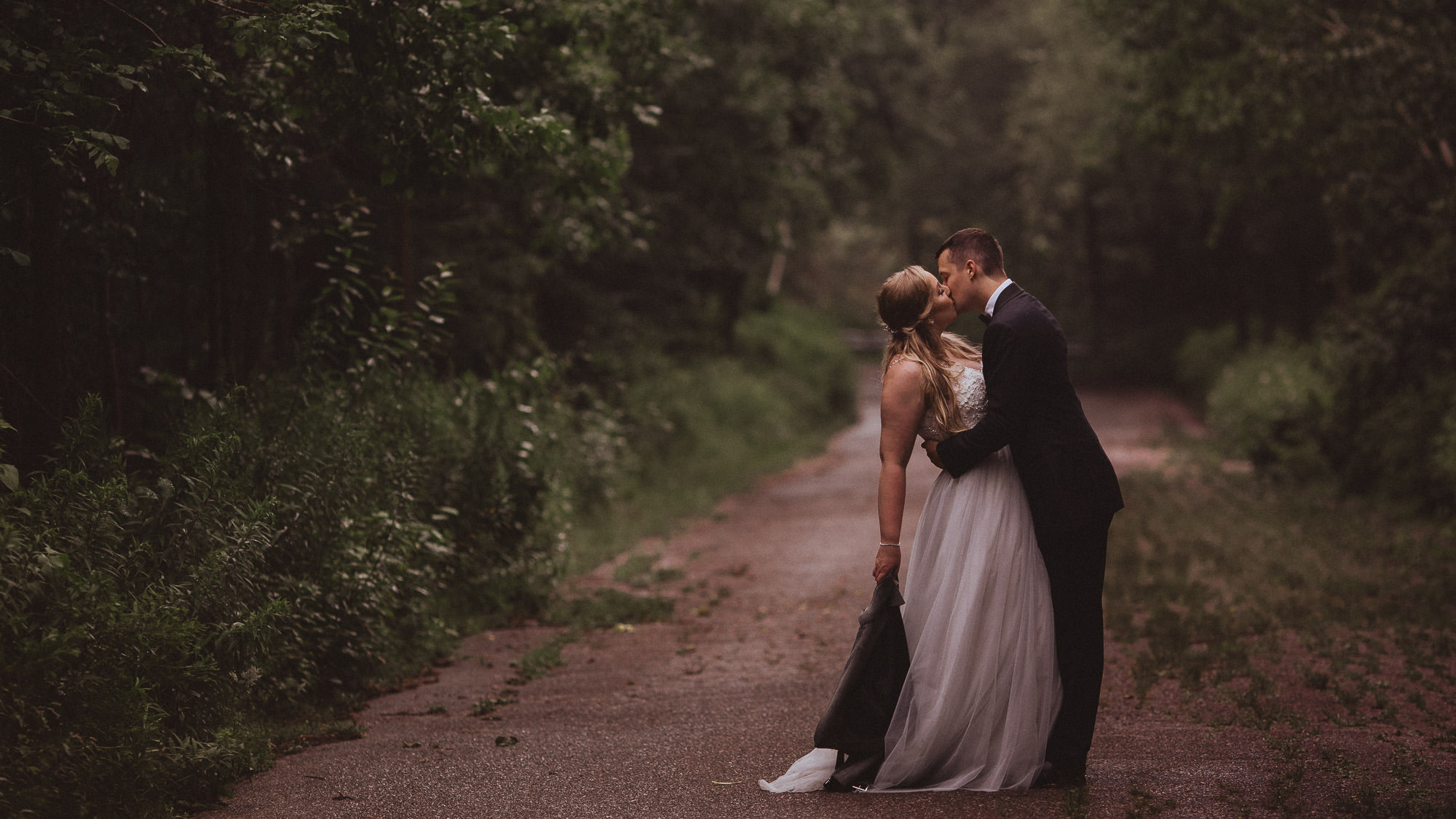 groom kisses bride on abandoned forested road