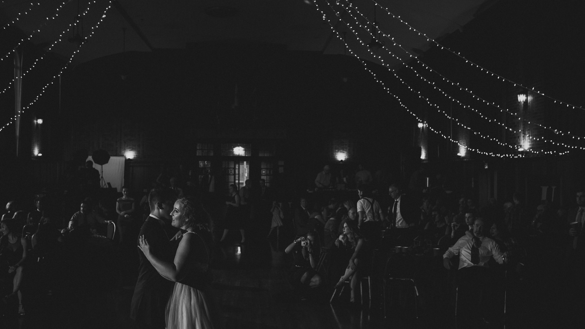 newlywed couple first dance black and white with string lights