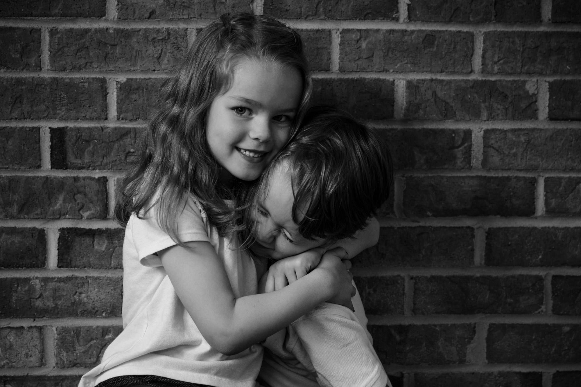 sister hugging brother tight