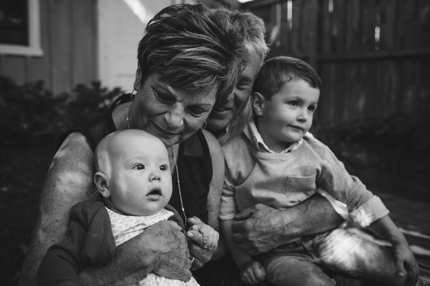 Black and white photo of grandparents holding 2 young grandchildren