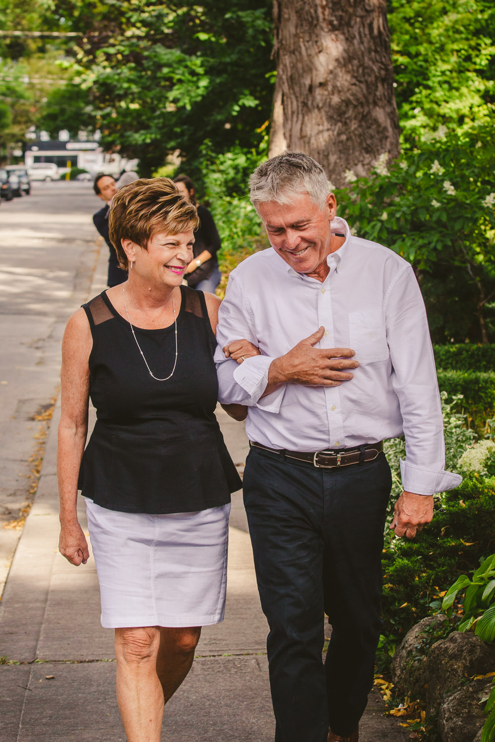 Grandparents walking on sidewalk smiling