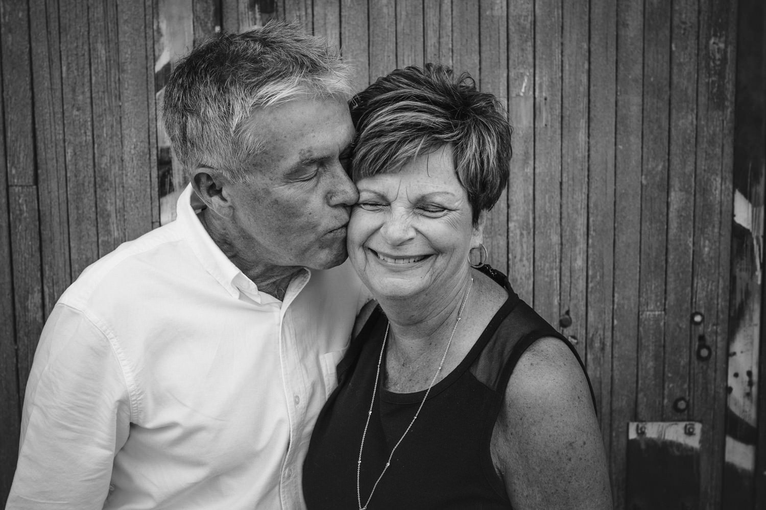 Man kissing woman on cheek black and white image