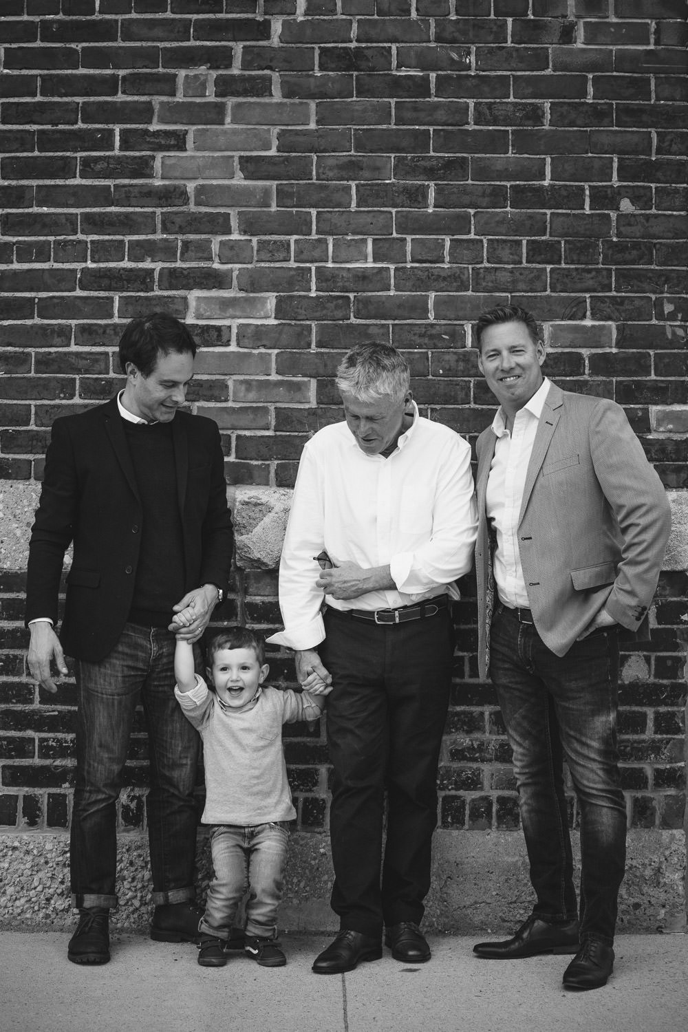 black and white image of 3 men and a little boy in front of brick wall