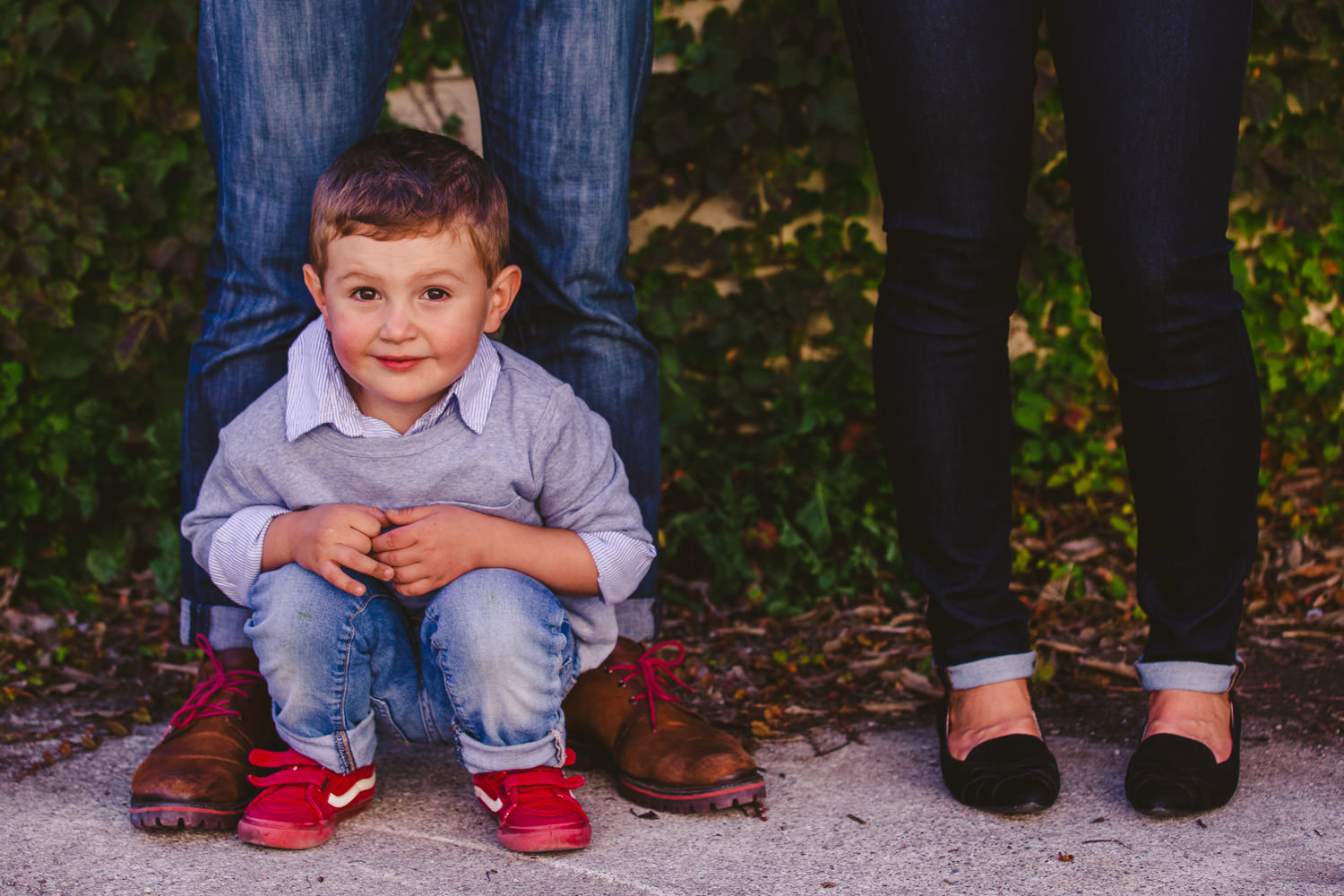 Little boy crouching between parents legs and feet