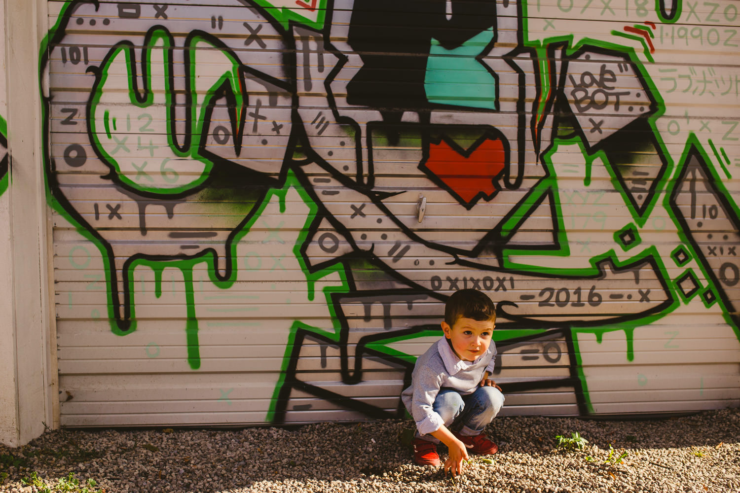 Little boy crouching in front of graffiti covered wall