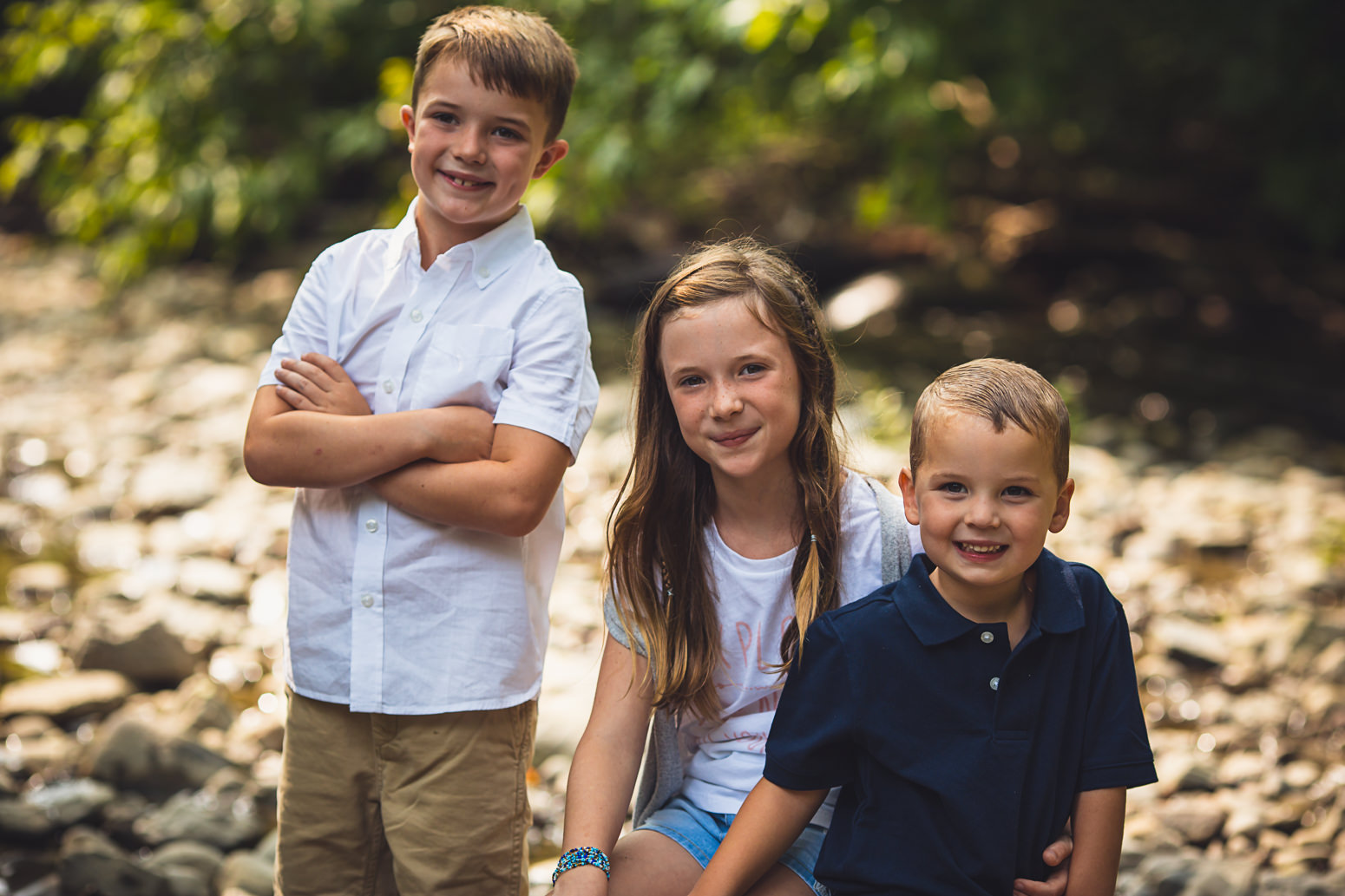 3 kids posing together in creek