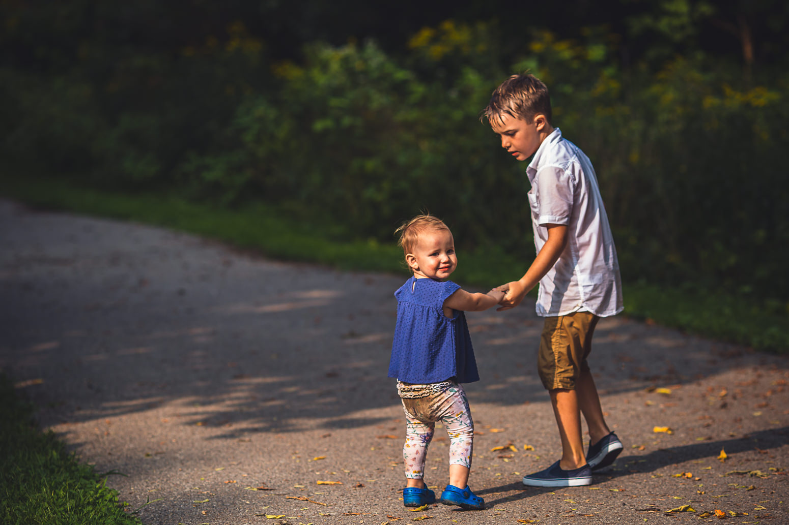 Brother holding baby sister's hand on walking path