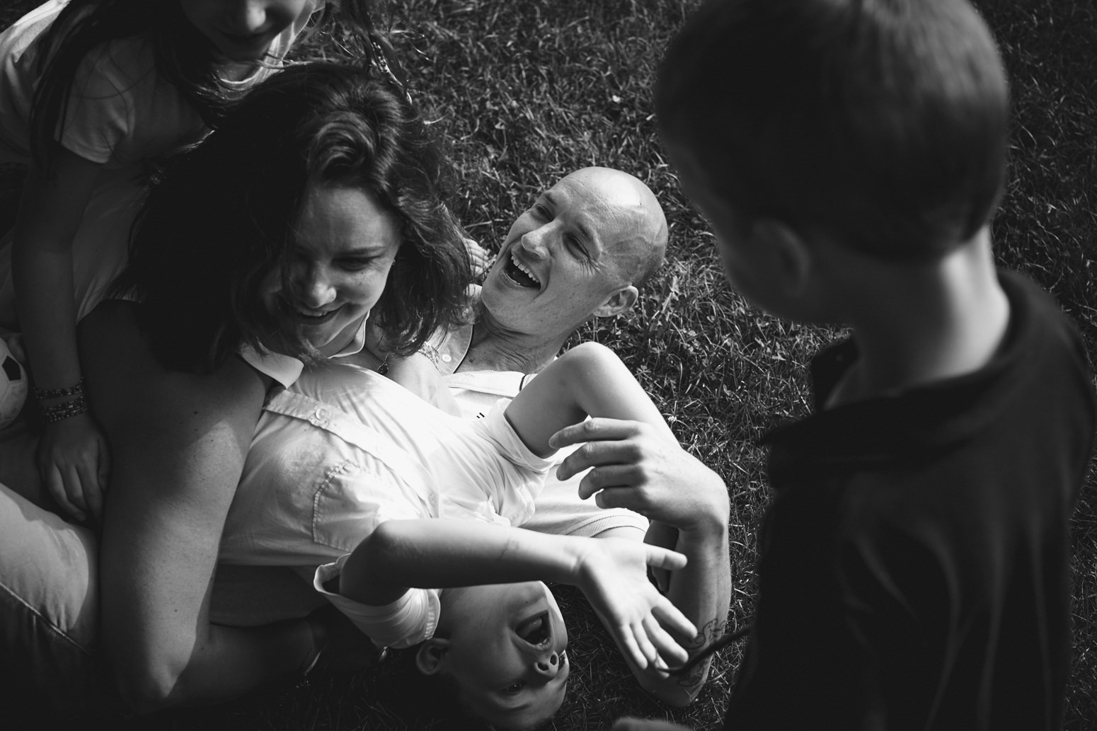 Black and white photo of family playing together on grass