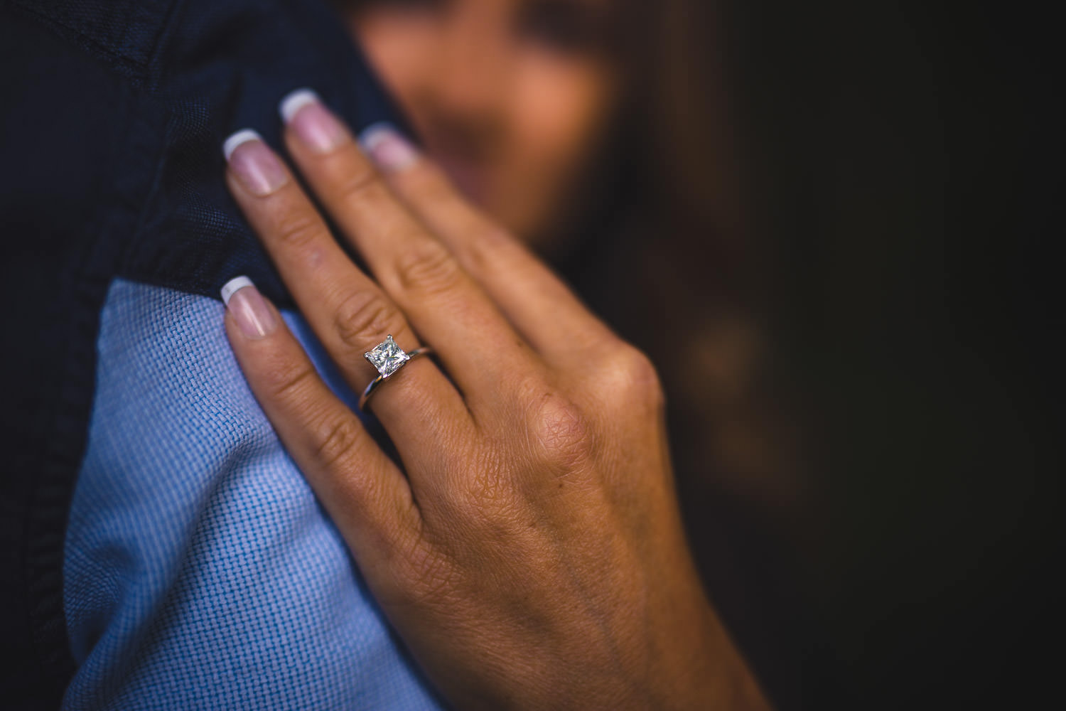 Woman's hand on man's shoulder showing off engagement ring