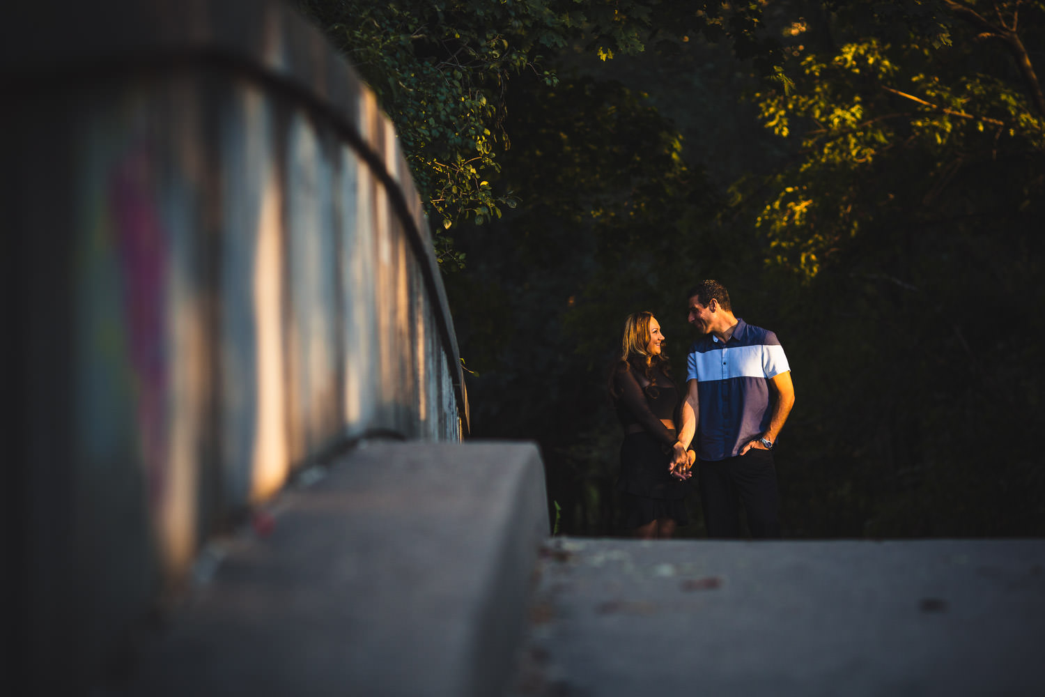Man and woman holding hands walking on concrete bridge