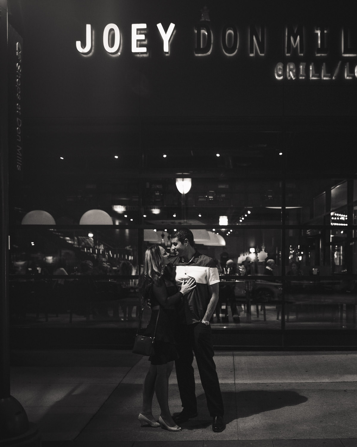 Man and woman standing in front of restaurant under a streetlight.