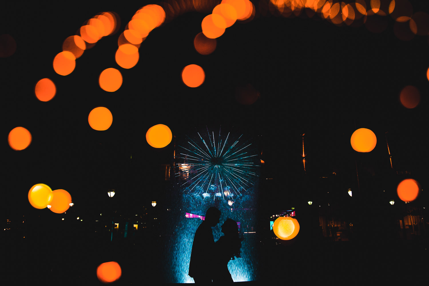 Silhouette of couple embracing in front of artistic water fountain