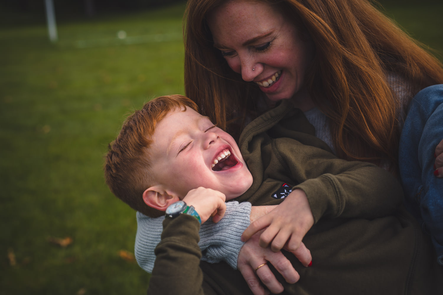 Mother tickles her son while laughing in a park