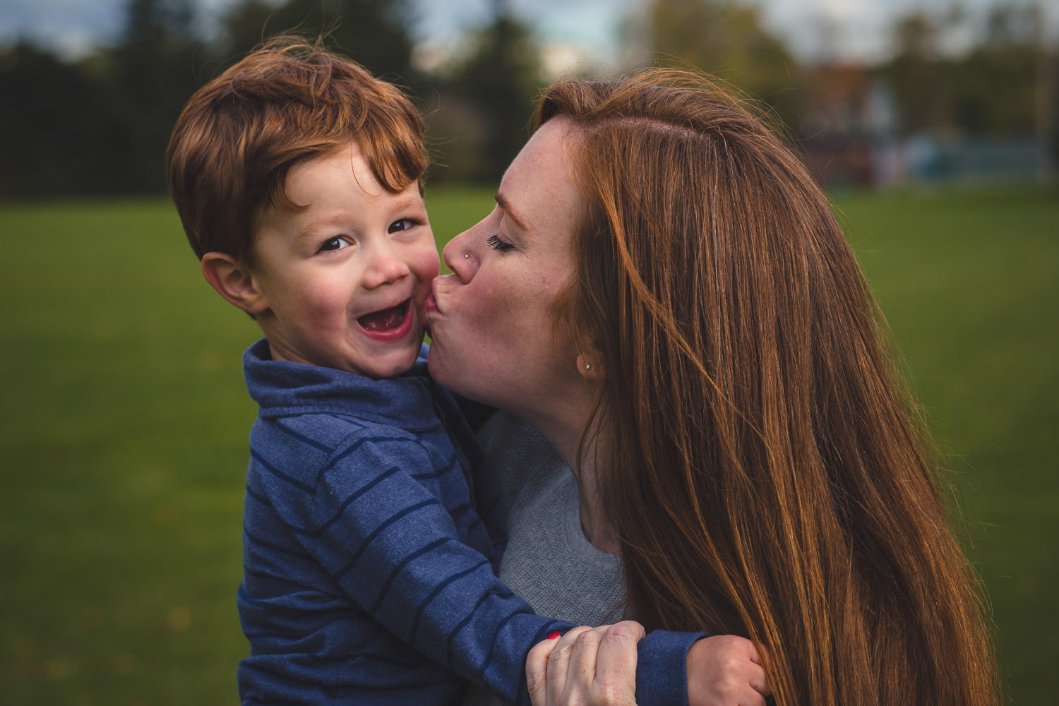 Mother gives son a kiss in the park