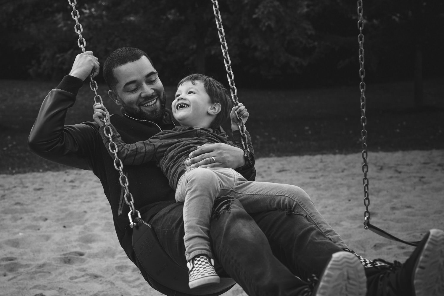 Father and son ride on swing together