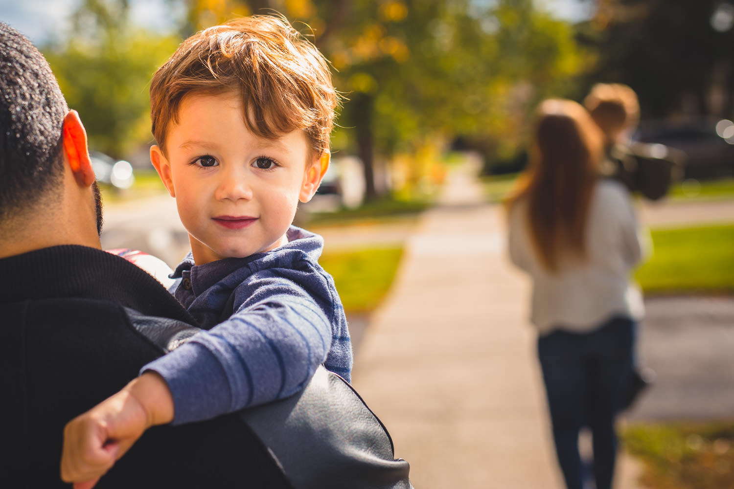 Little boy looks at camera while mom and brother walk ahead