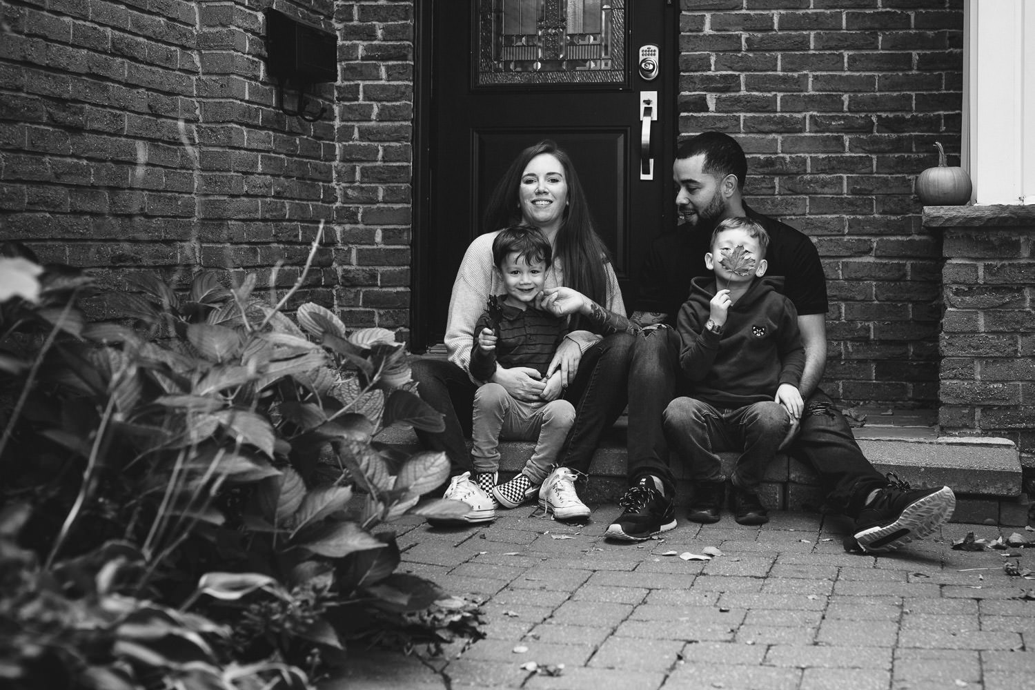 Family sits together on front porch