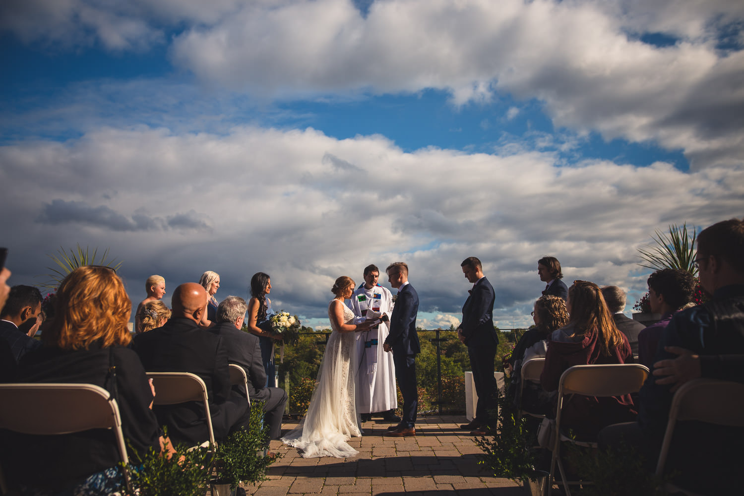 Wedding party stands at altar during ceremony under sunny skies