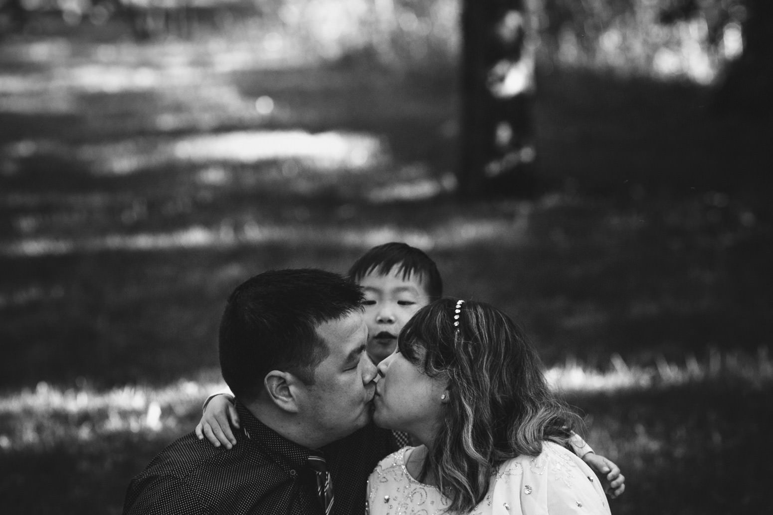 Mom and Dad kiss while son lurks behind them