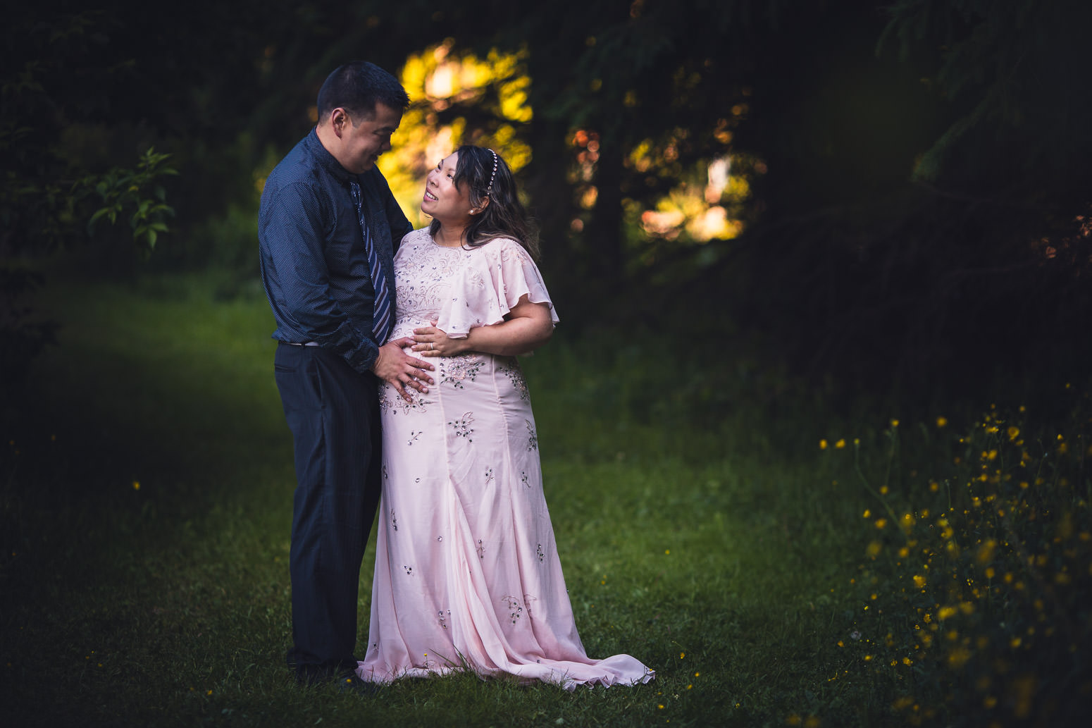 Maternity photo of husband and wife in grassy wooded setting