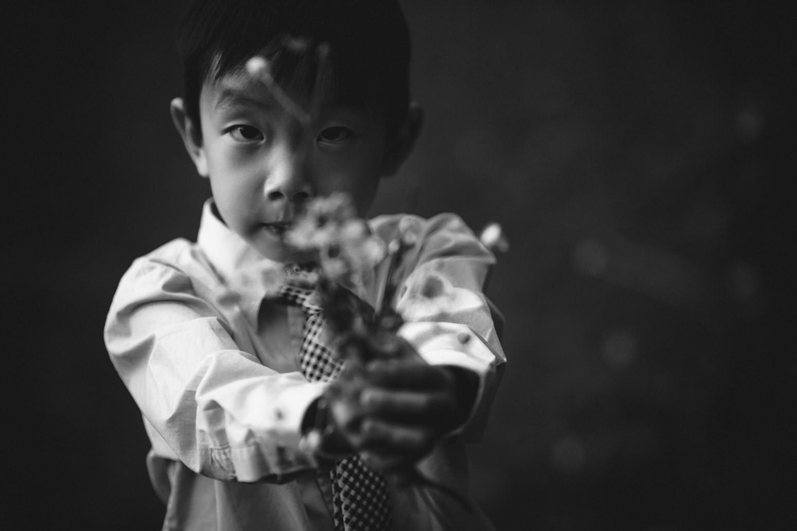 Black and white photo of boy holding flowers