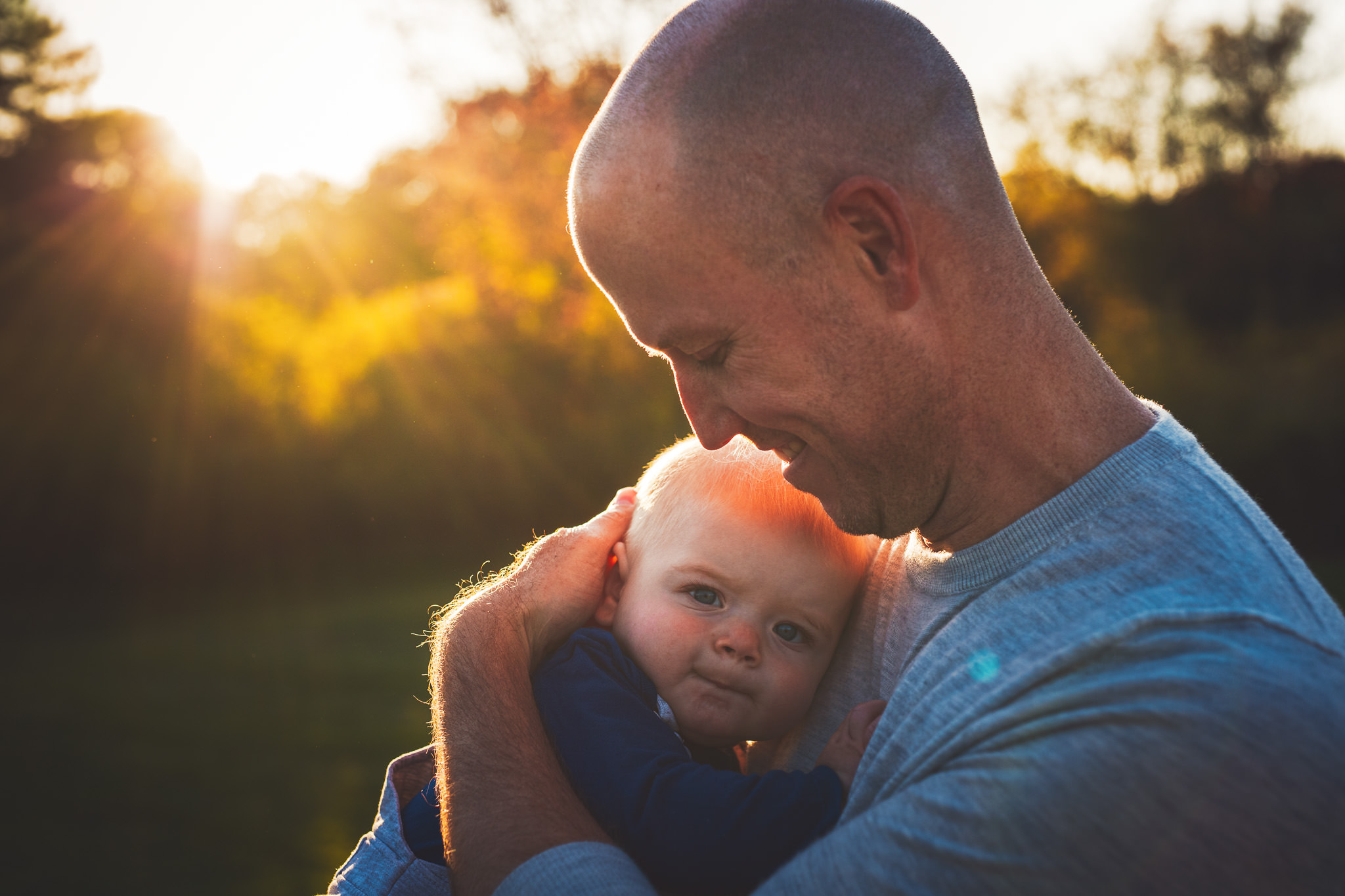 Father holds newborn son with sunset behind
